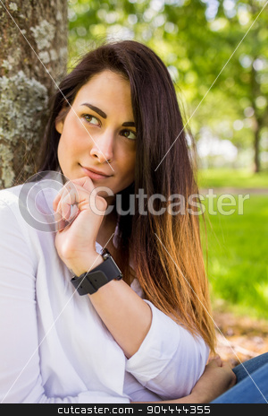 Beautiful brunette thinking in the park stock photo, Beautiful brunette thinking in the park on a sunny day by Wavebreak Media