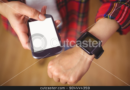 Pretty hipster using her smartphone and smartwatch stock photo, Pretty hipster using her smartphone and smartwatch high angle view by Wavebreak Media