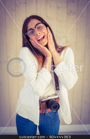 Pretty hipster using her vintage camera stock photo, Pretty hipster using her vintage camera on wooden planks background by Wavebreak Media