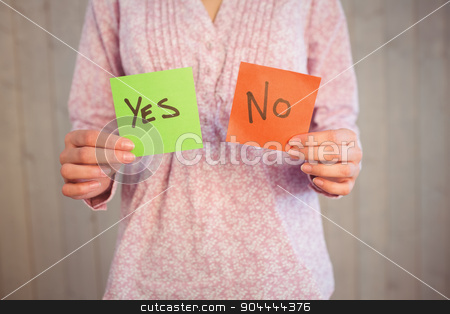 Woman holding yes and no cards stock photo, Woman holding yes and no cards on wooden planks background by Wavebreak Media