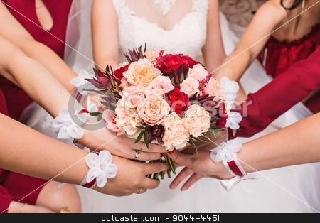 Close-up of a bride and her bridesmaids holding bouquet. stock photo, Close-up of a bride and her bridesmaids holding beautiful wedding bouquet. by Satura86