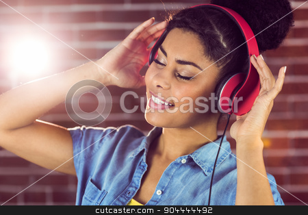 A smiling woman being transported by music stock photo, A smiling woman being transported by music on a brick wall by Wavebreak Media