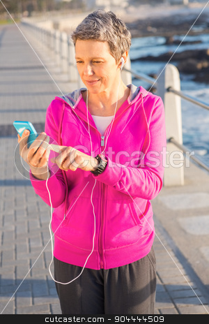 Smiling sporty woman enjoying music and holding phone stock photo, Smiling sporty woman enjoying music and holding phone at promenade by Wavebreak Media