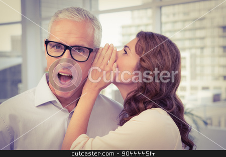 Casual businesswoman whispering secret to her colleague stock photo, Casual businesswoman whispering secret to her colleague in the office by Wavebreak Media