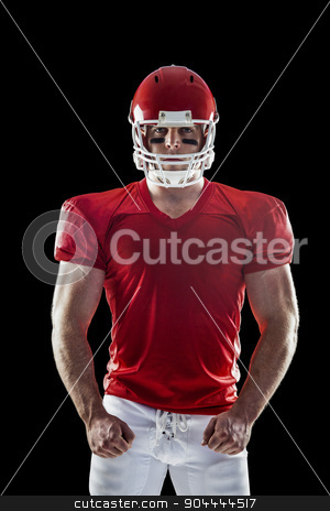 American football player looking at camera stock photo, American football player looking at camera on black background by Wavebreak Media