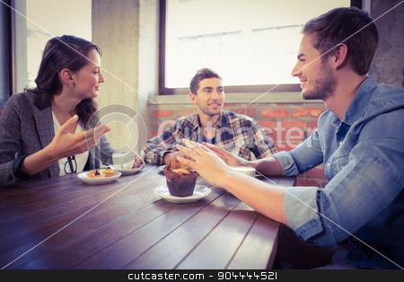 Smiling friends talking and enjoying coffee stock photo, Smiling friends talking and enjoying coffee at coffee shop by Wavebreak Media