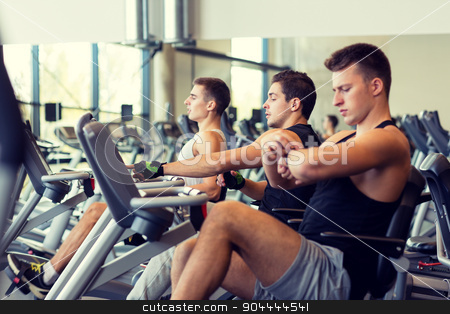 men working out on exercise bike in gym stock photo, sport, fitness, lifestyle, technology and people concept - men working out on exercise bike in gym by Syda Productions