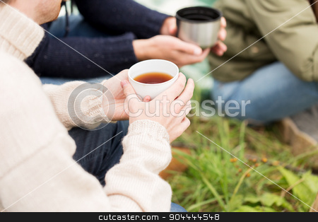 close up of hikers drinking tea from cups at camp stock photo, adventure, travel, tourism and people concept - close up of hikers drinking tea from cups at camp by Syda Productions