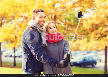 smiling couple with smartphone in autumn park stock photo, love, relationship, family and people concept - smiling couple hugging and taking selfie with smartphone and monopod in autumn park by Syda Productions