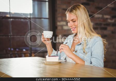 Smiling blonde enjoying cake and coffee stock photo, Smiling blonde enjoying cake and coffee at coffee shop by Wavebreak Media