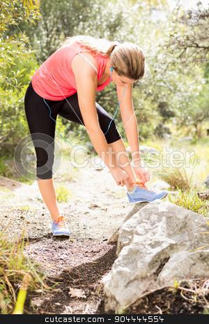 Blonde athlete tying her shoelace stock photo, Blonde athlete tying her shoelace in the nature by Wavebreak Media
