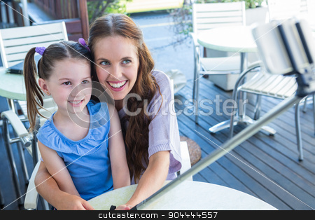 Mother and daughter using selfie stick at cafe terrace stock photo, Mother and daughter using selfie stick at cafe terrace on a sunny day by Wavebreak Media