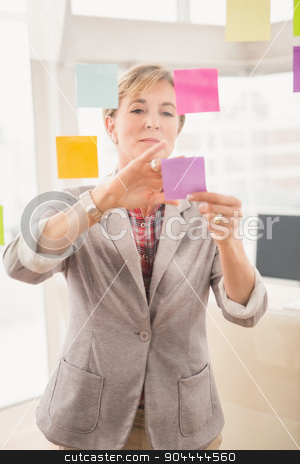 Casual businesswoman putting sticky notes on glass stock photo, Casual businesswoman putting sticky notes on glass in the office by Wavebreak Media