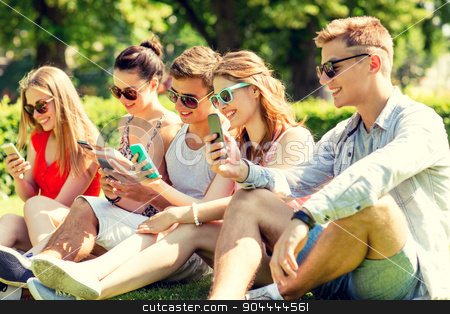 smiling friends with smartphones sitting on grass stock photo, friendship, leisure, summer, technology and people concept - group of smiling friends with smartphones sitting on grass in park by Syda Productions