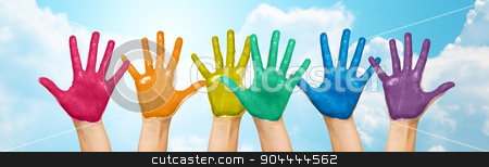 palms of human hands painted in rainbow colors stock photo, people, gay pride, creativity and art concept - palms of human hands painted in rainbow colors over blue sky and clouds background by Syda Productions