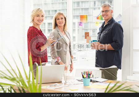 Standing business team looking at the camera stock photo, Portrait of standing business team  holding a tablet at office by Wavebreak Media