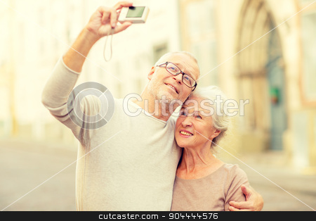 senior couple photographing on city street stock photo, age, tourism, travel, technology and people concept - senior couple with camera taking selfie on street by Syda Productions