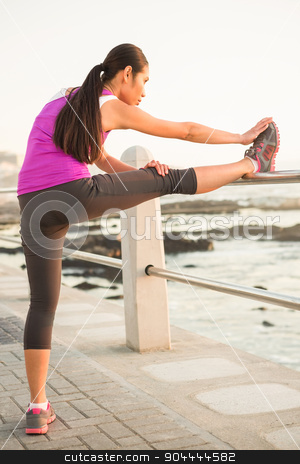 Fit woman stretching leg on railing stock photo, Fit woman stretching leg on railing at promenade by Wavebreak Media