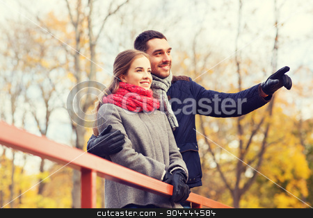 smiling couple hugging on bridge in autumn park stock photo, love, gesture, family, season and people concept - smiling couple hugging on bridge in autumn park by Syda Productions
