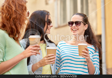 happy young women drinking coffee on city street stock photo, vacation, weekend, takeaway drinks, leisure and friendship concept - smiling happy young women or teenage girls drinking coffee from disposable paper cups on city street by Syda Productions
