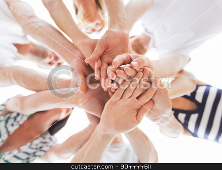 close up of friends with hands on top stock photo, vacation, travel, sea, friendship and people concept - close up of happy friends with hands on top on beach by Syda Productions