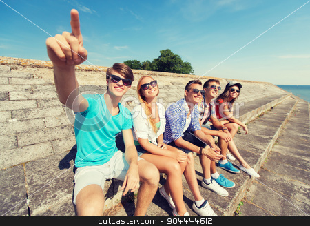 group of smiling friends sitting on city street stock photo, friendship, leisure, summer, gesture and people concept - group of smiling friends sitting and pointing finger on city street by Syda Productions
