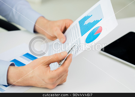 close up of businessman hands with charts stock photo, business, people and statistics concept - close up of businessman hands with chart and pen at office by Syda Productions
