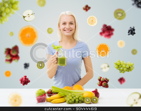smiling woman drinking juice or shake at home stock photo, healthy eating, vegetarian food, diet, detox and people concept - smiling woman drinking green vegetable juice or shake from glass over fruits and berries on gray background by Syda Productions