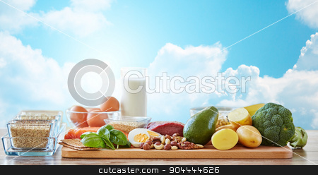 close up of different natural food items on table stock photo, balanced diet, cooking, culinary and food concept - close up of vegetables, fruits and meat on wooden table over blue sky and clouds background by Syda Productions