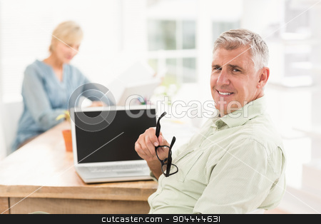 Smiling businessman looking at the camera stock photo, Portrait of a smiling businessman working on laptop at office by Wavebreak Media