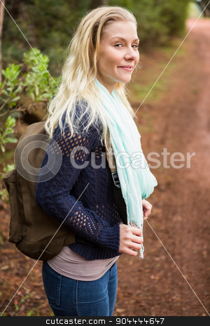 Smiling female hiker waiting by the side of the road stock photo, Profile view of a female hiker waiting by the side of the road by Wavebreak Media