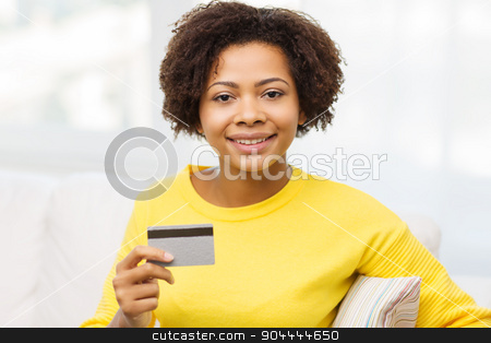 happy african woman with credit or debit card stock photo, people, bank, shopping and e-money concept - happy african american young woman sitting on sofa with credit or debit card at home by Syda Productions