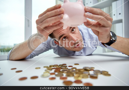 businessman with piggy bank and coins at office stock photo, business, people, finances, crisis and money saving concept - businessman shaking piggy bank and getting coins at office by Syda Productions