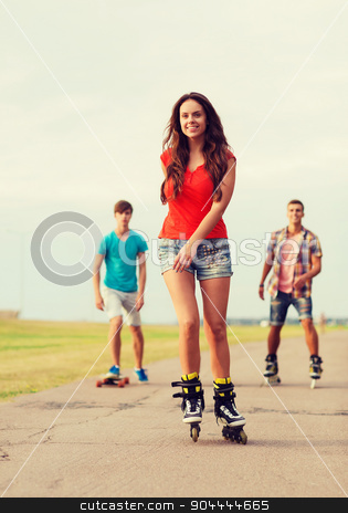 group of smiling teenagers with roller-skates stock photo, holidays, vacation, love and friendship concept - group of smiling teenagers with roller skates and skateboard riding outdoors by Syda Productions