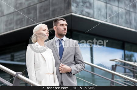 serious businessmen standing over office building stock photo, business, partnership, success and people concept - serious businessman and businesswoman standing over office building by Syda Productions
