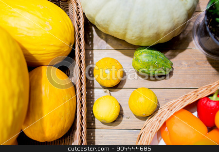 vegetables in baskets on table at market or farm stock photo, sale, farming, agriculture and eco food concept - ripe vegetables in baskets on table at grocery market or farm by Syda Productions