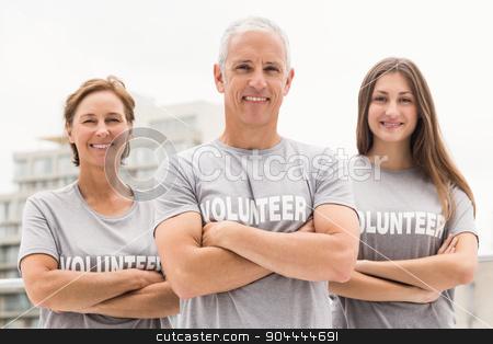 Smiling volunteers with arms crossed stock photo, Portrait of smiling volunteers with arms crossed on roof of building by Wavebreak Media