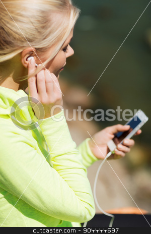 woman listening to music outdoors stock photo, sport and lifestyle concept - woman doing sports and listening to music outdoors by Syda Productions