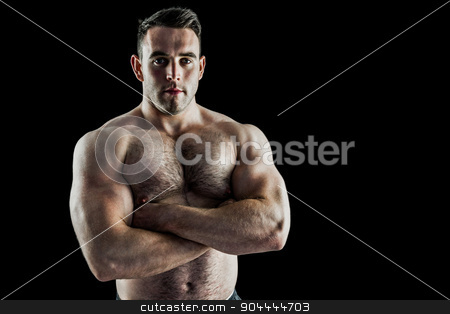 Strong bodybuilder with arms crossed stock photo, Strong bodybuilder with arms crossed on black background by Wavebreak Media