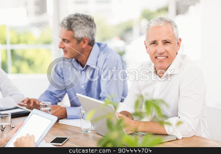 Smiling businessman during a meeting stock photo, Portrait of smiling businessman during a meeting in the office by Wavebreak Media