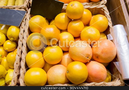 ripe grapefruits at food market stock photo, sale, shopping, vitamin c and healthy food concept - ripe grapefruits in basket with nameplate at grocery market by Syda Productions