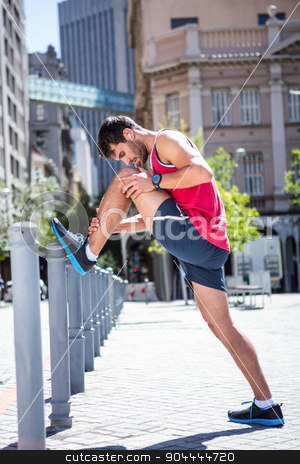 Handsome athlete doing leg stretching on a stake stock photo, Handsome athlete doing leg stretching on a stake on a sunny day by Wavebreak Media