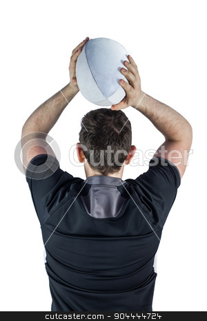 Back turned rugby player throwing a ball stock photo, Back turned rugby player throwing a ball on a white background by Wavebreak Media