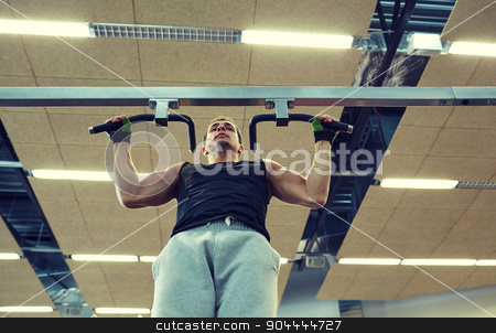 young man exercising in gym stock photo, sport, fitness, lifestyle and people concept - young man doing pull-ups in gym by Syda Productions