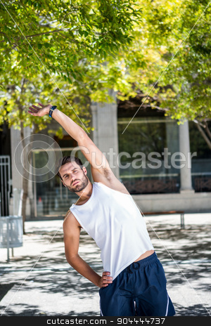 Handsome athlete warming up stock photo, Handsome athlete warming up in the city by Wavebreak Media