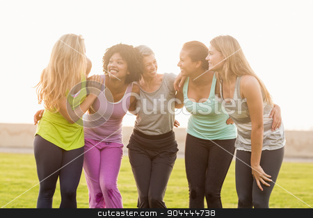 Smiling sporty women with arms around each other stock photo, Smiling sporty women with arms around each other in parkland by Wavebreak Media