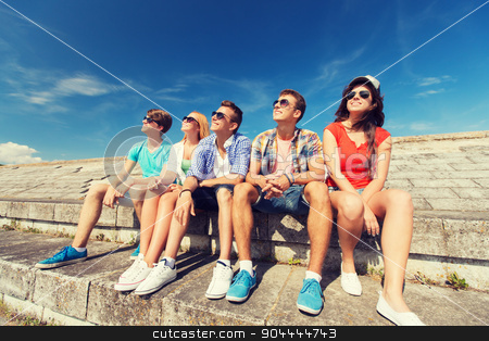 group of smiling friends sitting on city street stock photo, friendship, leisure, summer and people concept - group of smiling friends sitting on city street by Syda Productions