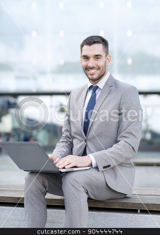 smiling businessman working with laptop outdoors stock photo, business, education, technology and people concept - smiling businessman working with laptop computer on city street by Syda Productions