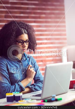 Casual businesswoman looking in her laptop stock photo,  Casual businesswoman looking in her laptop in her office by Wavebreak Media