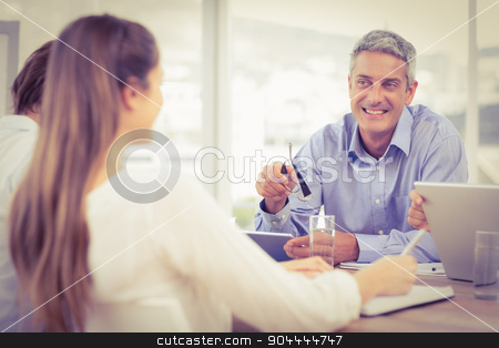 Smiling businessman talking while meeting stock photo, Smiling businessman talking while meeting in the office by Wavebreak Media